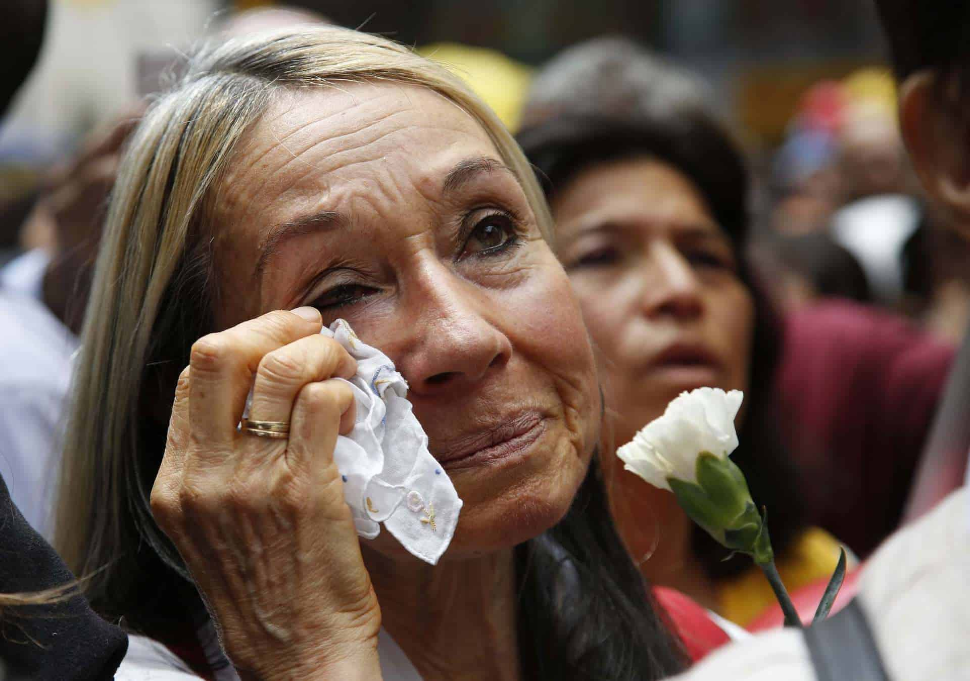 A woman cries as she watches a live broadcast from Havana of the ceremony of the agreement between Colombian president and the head of FARC rebels on a cease-fire and rebel disarmament deal, in Bogota, Colombia, Thursday, June 23, 2016. The deal moves the country closer to the end of a 52-year war that has left more than 220,000 people dead. (AP Photo/Fernando Vergara)